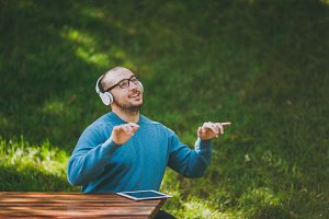 Man plays with fingers in air like piano. Student in casual blue shirt glasses sitting at table with headphones, tablet in city park, listen music, rest outdoors on nature. Lifestyle leisure concept.