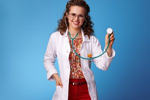 happy paediatrist woman using stethoscope on blue