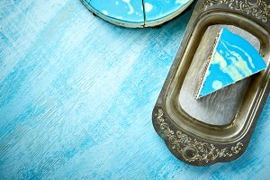 piece of mousse cake with blue glaze on a looking like silver, vintage metal dish on the white-blue wooden background