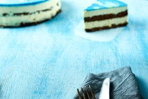 sliced cake and piece of mousse cake with blue glaze on the white-blue wooden background