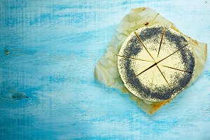 sliced mousse cake with yellow glaze and poppy seeds on the white-blue wooden background
