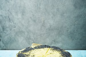 sliced mousse cake with yellow glaze and poppy seeds on the gray concrete background