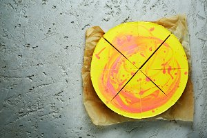 sliced mousse cake with yellow red glaze on the gray concrete background