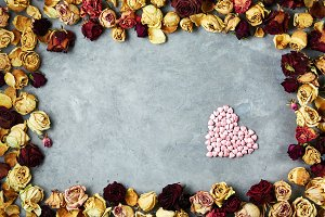 big heart of little decorative hearts in frame from dried roses buds on the gray concrete background
