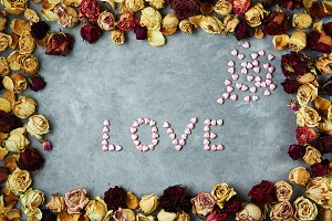 word Love from small decorative hearts in frame from dried roses buds on the gray concrete background