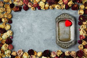 vintage metal dish in frame from dried roses buds on the gray concrete background