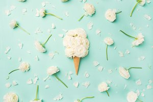 Waffle cone with white buttercup flowers over light blue background