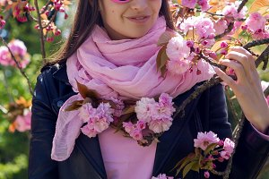 portrait of a girl in pink sunglasses standing in pink cherry blossoms