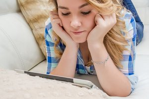 Teen using tablet pc liying on sofa