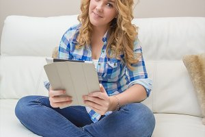 Teen using tablet pc sitting on sofa