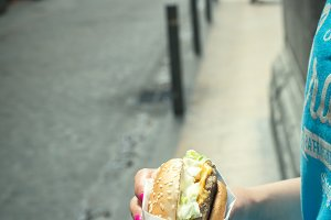 Stylish hipster woman wering blue holds a hamburger in hands. Summer