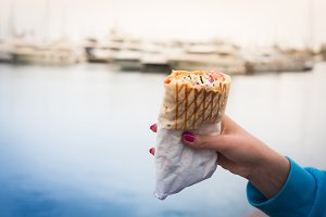 Stylish hipster woman holding a doner kebab in her hand. Sea background