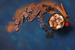 Pieces of chocolate and hot coffee with marshmallows on a blue beautiful background. Top view, space for text.