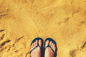 Woman legs in slippers on yellow sand background. Blue flip flops on beach. Copy space, top view. Holiday and travel concept