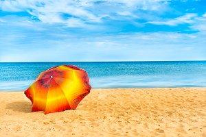 Orange umbrella on golden beach