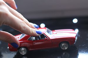Woman hand with manicure and toy car