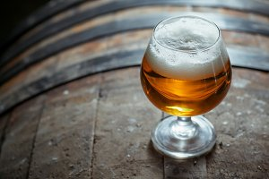 Snifter beer glass on a barrel