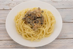 Pasta with fried champignons in a white plate.