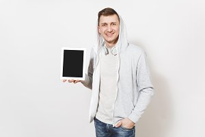 Young handsome smiling man in t-shirt and light sweatshirt with hood with headphones holds tablet pc computer with blank screen for copy space isolated on white background. Concept of technology