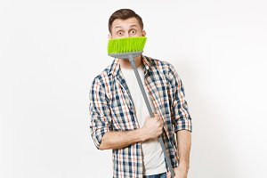 Young smiling housekeeper man in checkered shirt holding, hiding and sweeping with green broom isolated on white background. Male doing house chores. Copy space for advertisement. Cleanliness concept.