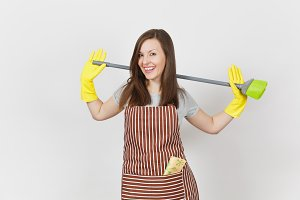 Young smiling housewife in striped apron, yellow gloves isolated on white background. Housekeeper woman cleaning maid holding and sweeping with broom. Copy space for advertisement. Advertising area.