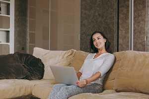 Beautiful young woman at home sitting on the sofa, relaxing in her living room and working with laptop