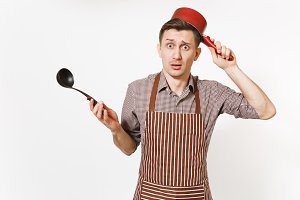 Young puzzled fun man chef or waiter in striped brown apron, shirt holding red empty stewpan black ladle isolated on white background. Male housekeeper or houseworker. Kitchenware and cuisine concept.