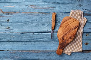 Cutting board and knife on blue wooden background