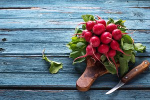 Fresh ripe radishes on blue table