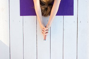 Woman practicing outdoors on violet yoga mat. Overhead close up of female hands in mudra on white wooden background.