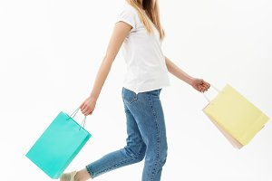 Shopping and Lifestyle Concept: Attractive young caucasain woman holding shopping bags and walking in studio. Full length portrait. Isolated on the white background.