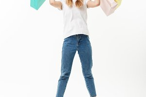 Full length portrait of a happy pretty girl holding shopping bags while jumping and looking at camera isolated over white background