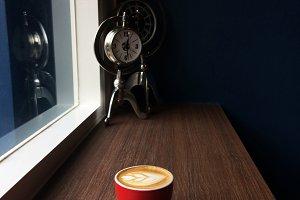 Red cup of cappuccino coffee in the morning time with vintage clock background.