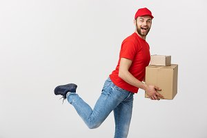 Delivery Concept - Handsome caucasian delivery man rush running for delivering a package for customer. Isolated on Grey studio Background. Copy Space.