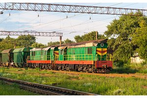 Two shunters with freight train at a station