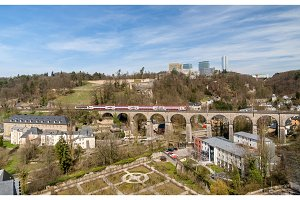 Train on viaduct in Luxembourg against background of European or