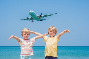 Two happy boys on the beach and a landing plane. Traveling with children concept