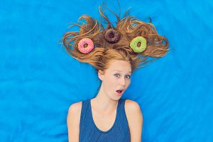 Young woman with donuts in her hair. Multicolored donuts. Harm of sweet