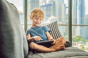 Boy uses a tablet at home on the couch in the background of a window with skyscrapers. Modern children in the megalopolis use a tablet concept
