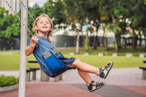Funny kid boy having fun with chain swing on outdoor playground. child swinging on warm day. Active leisure with kids. Boy wearing casual colorful school kid clothes