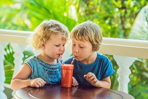 Children boy and girl drink orange smoothie from papaya