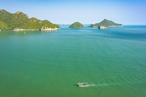 Aerial landscape of tropical islands and boat cruising the sea