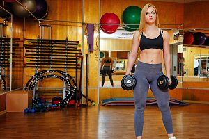 Girl in gym with dumbbells