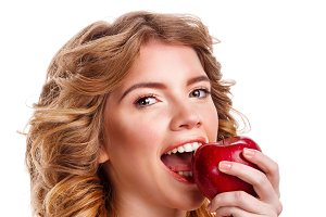 Girl with curly hair bit red apple