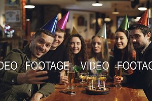 Happy young people in birthday party hats are recording video with smartphone sitting at table in bar. They are posing, laughing and clapping hands.