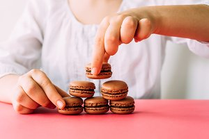 Woman placing macaroons on heap on pink table