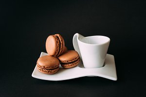 Set of cup of coffee and macaroons against black background
