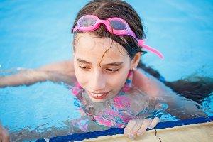 Smiling teenage girl having fun in swimming pool