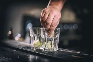 Barman hand squeezes lime juice