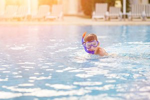 Small boy having fun with mask in swimming pool